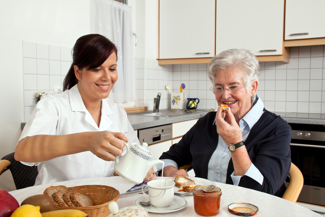 Caregiver serving breakfast to female client