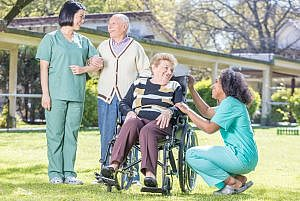 Senior couple with caregivers
