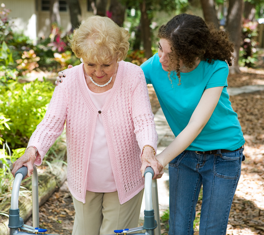 Woman outside with caregiver assisting