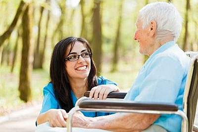 Caregiver and client laughing outdoors