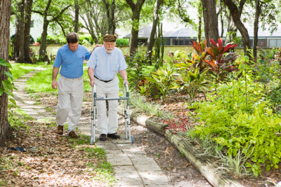 Senior male client outdoors with caregiver